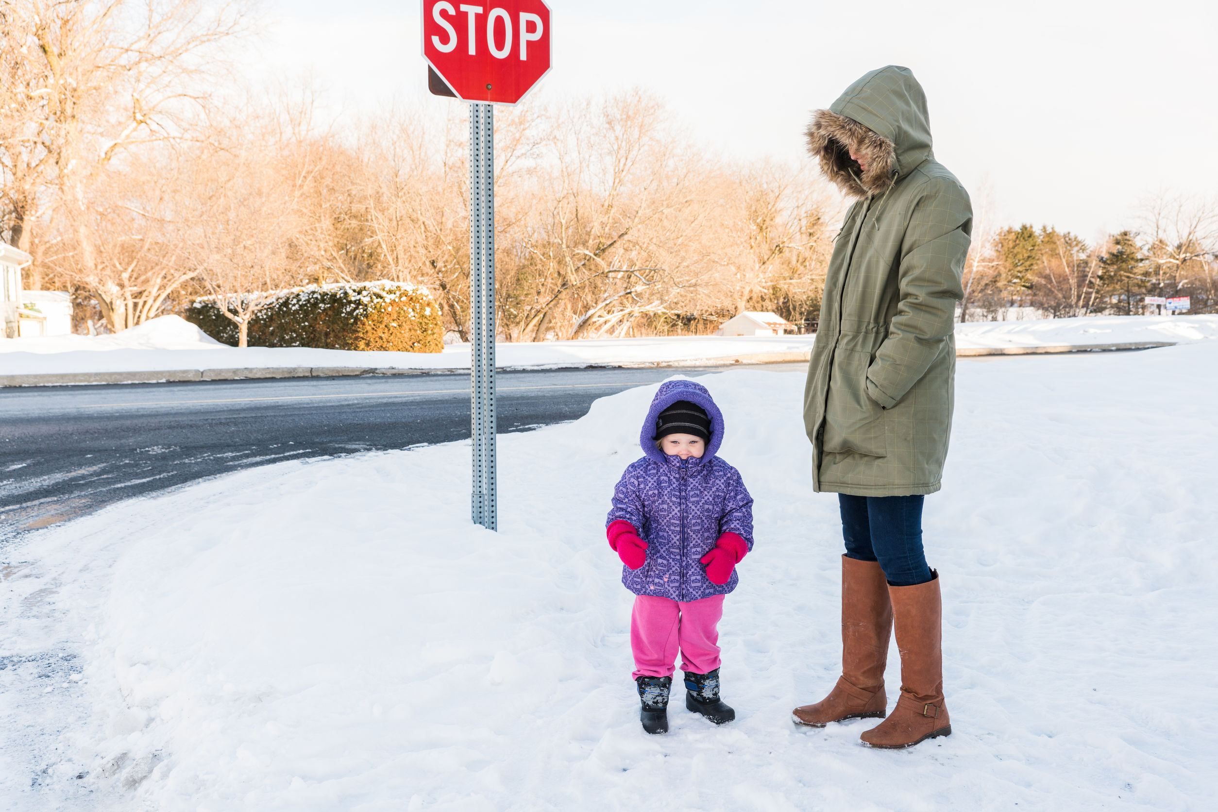 Child and parent in snow standing by a stop sign