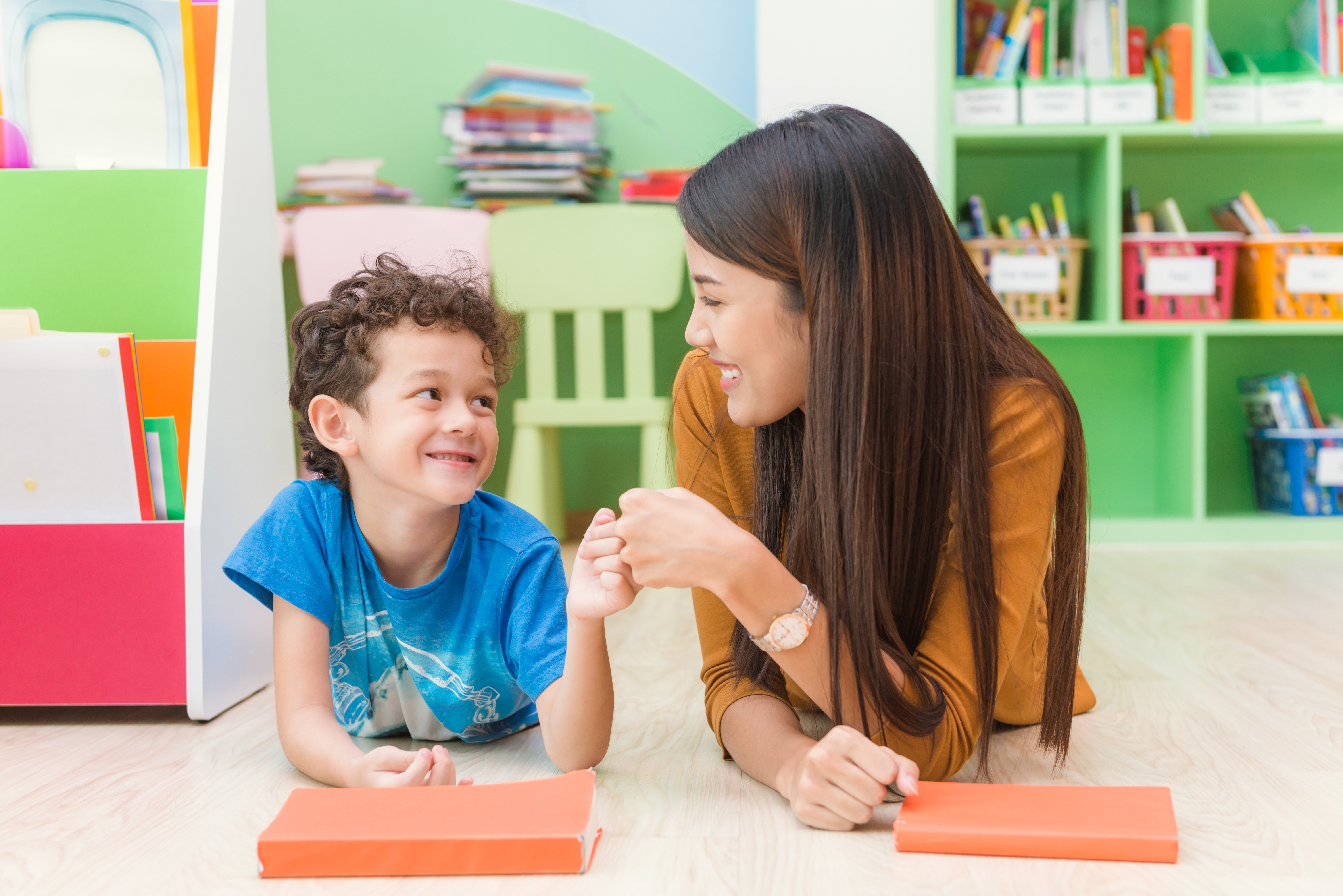 Young cheerful woman teacher teaching playful kid at colorful classroom.