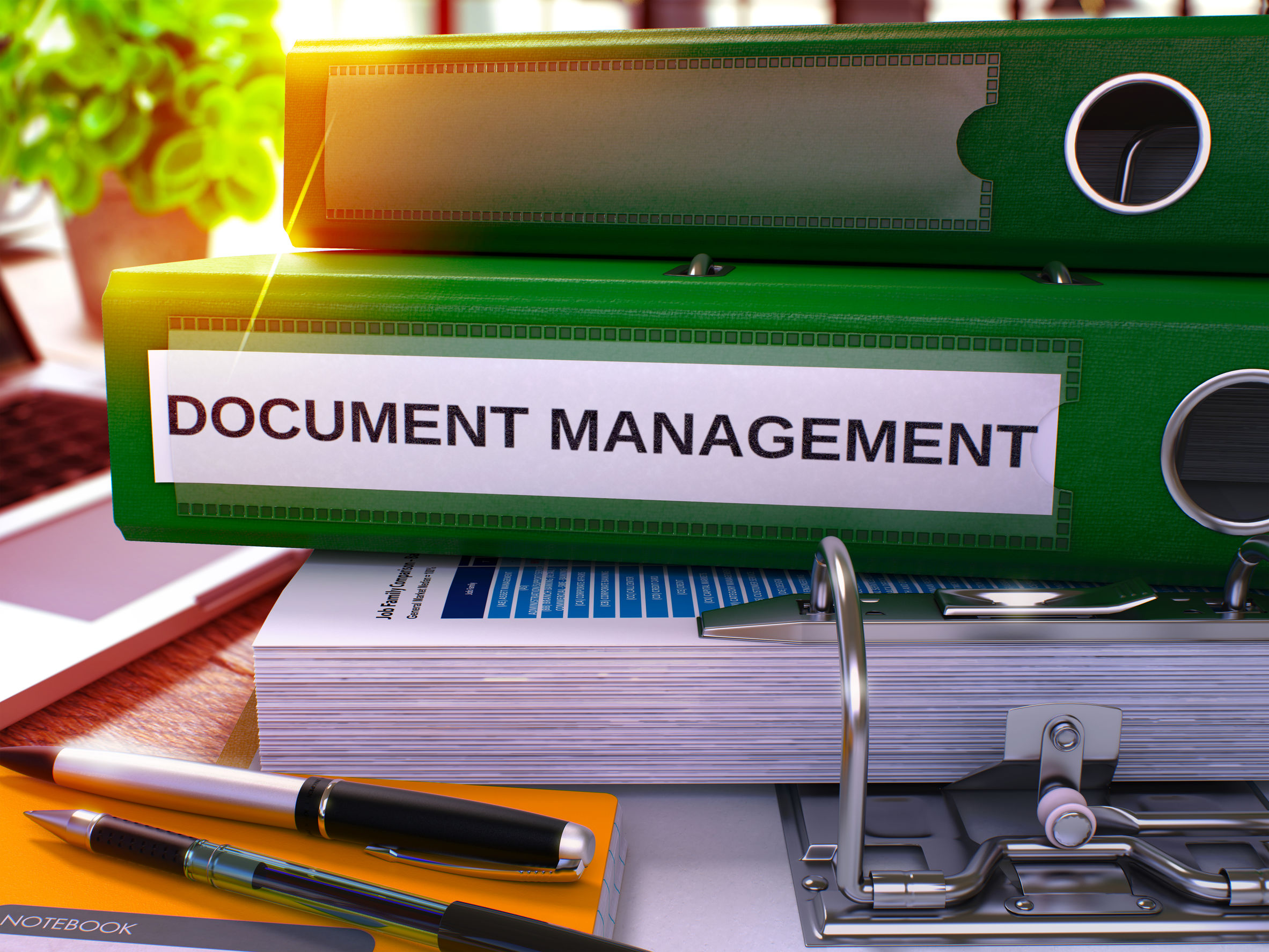 """Stack of binders with the words """"Document Management"""" on them."""