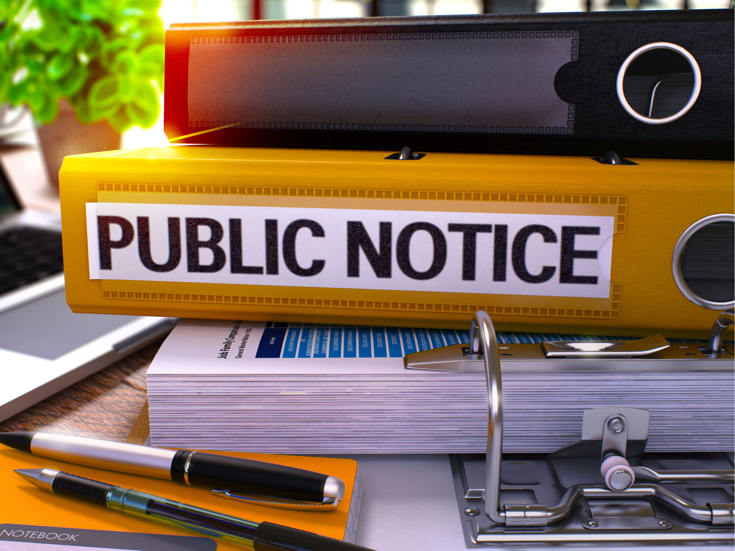 """stack of binders with the words """"Public Notice """" on one of them."""