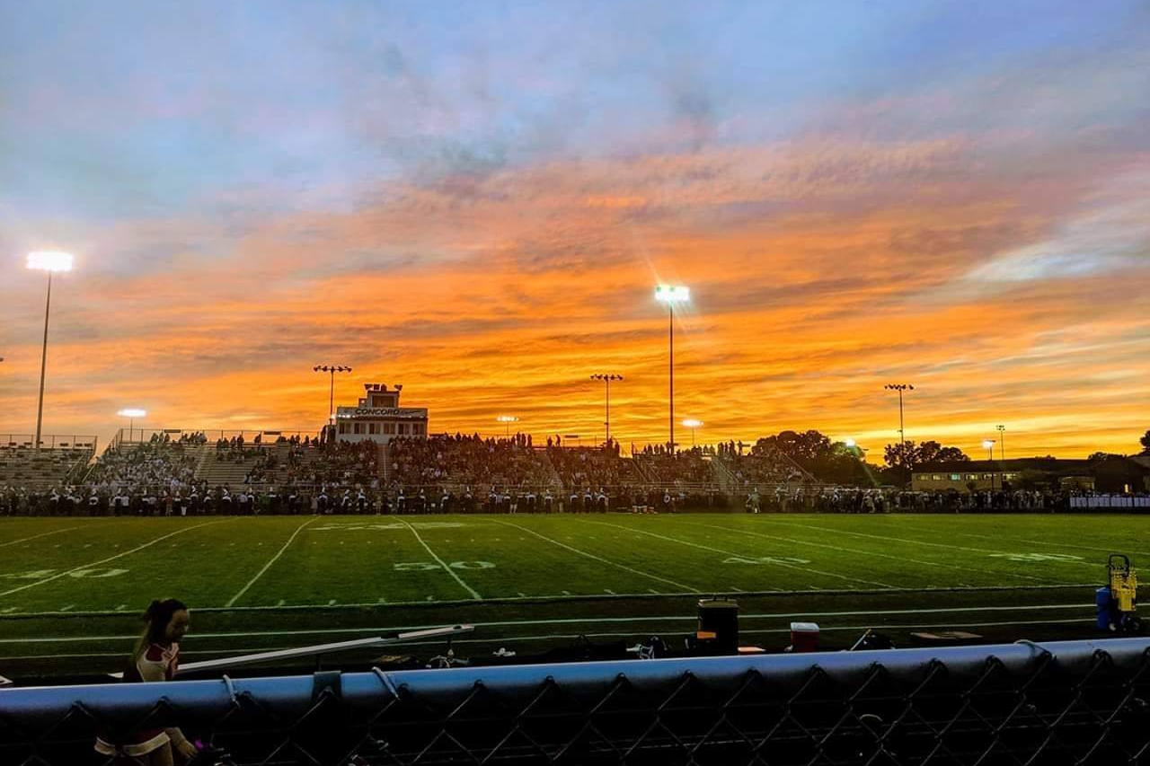 A picture of a sunrise over an athletic field