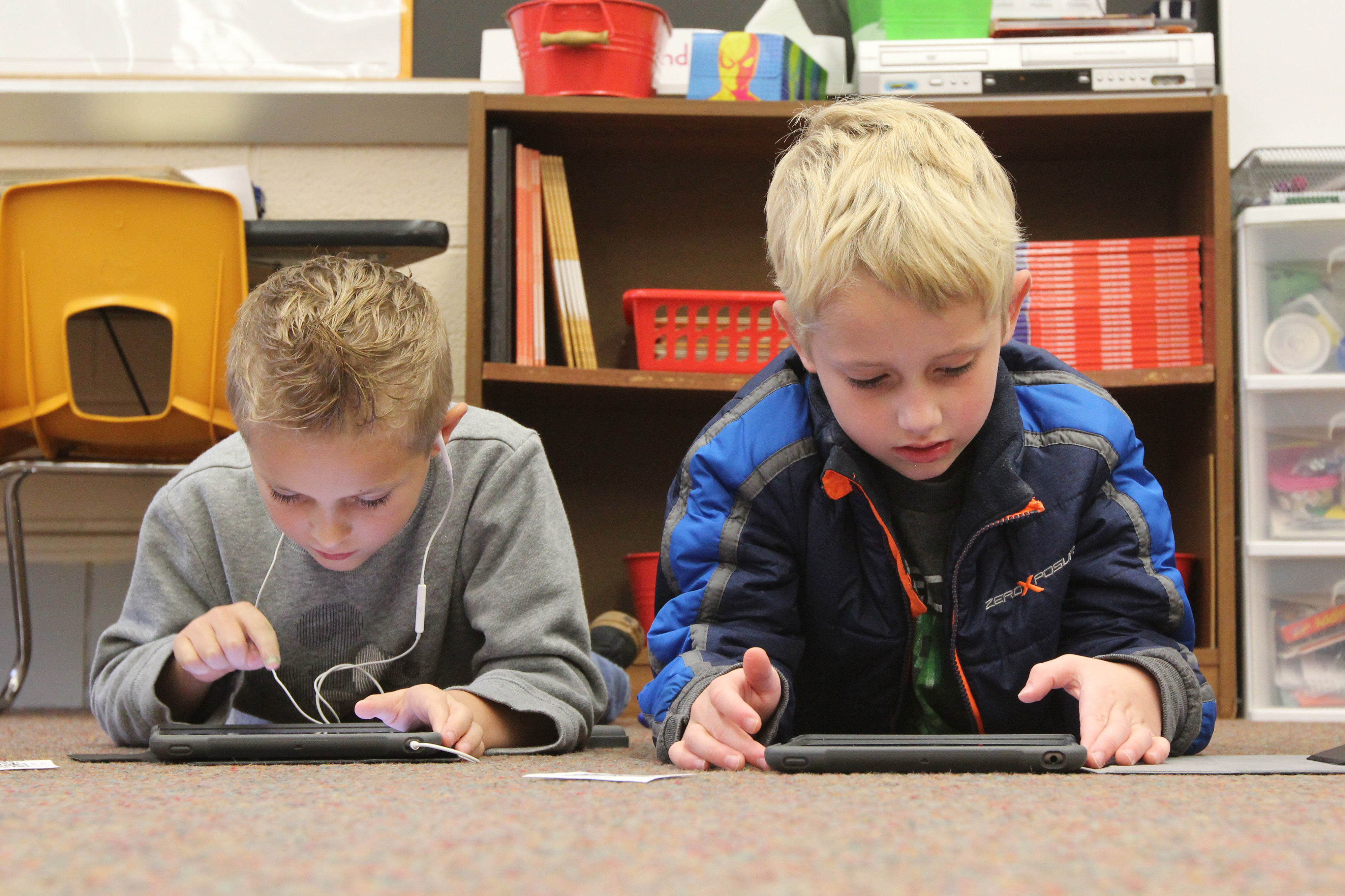 Two children use tablets