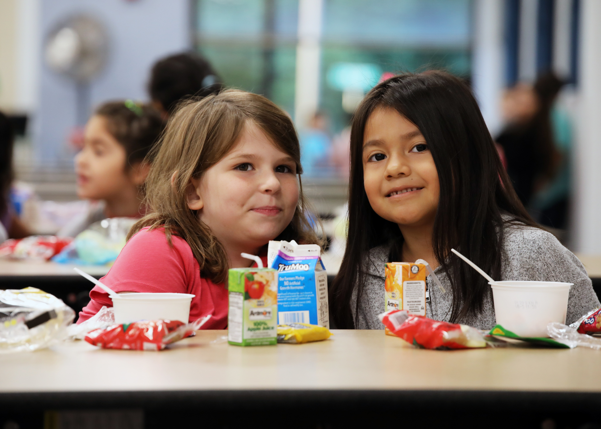 Two children pose for a picture in the cafeteria