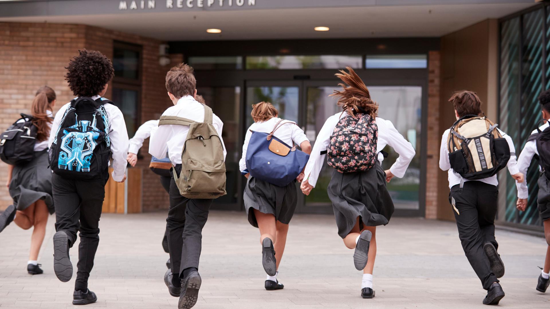 Kids in uniform running into school building
