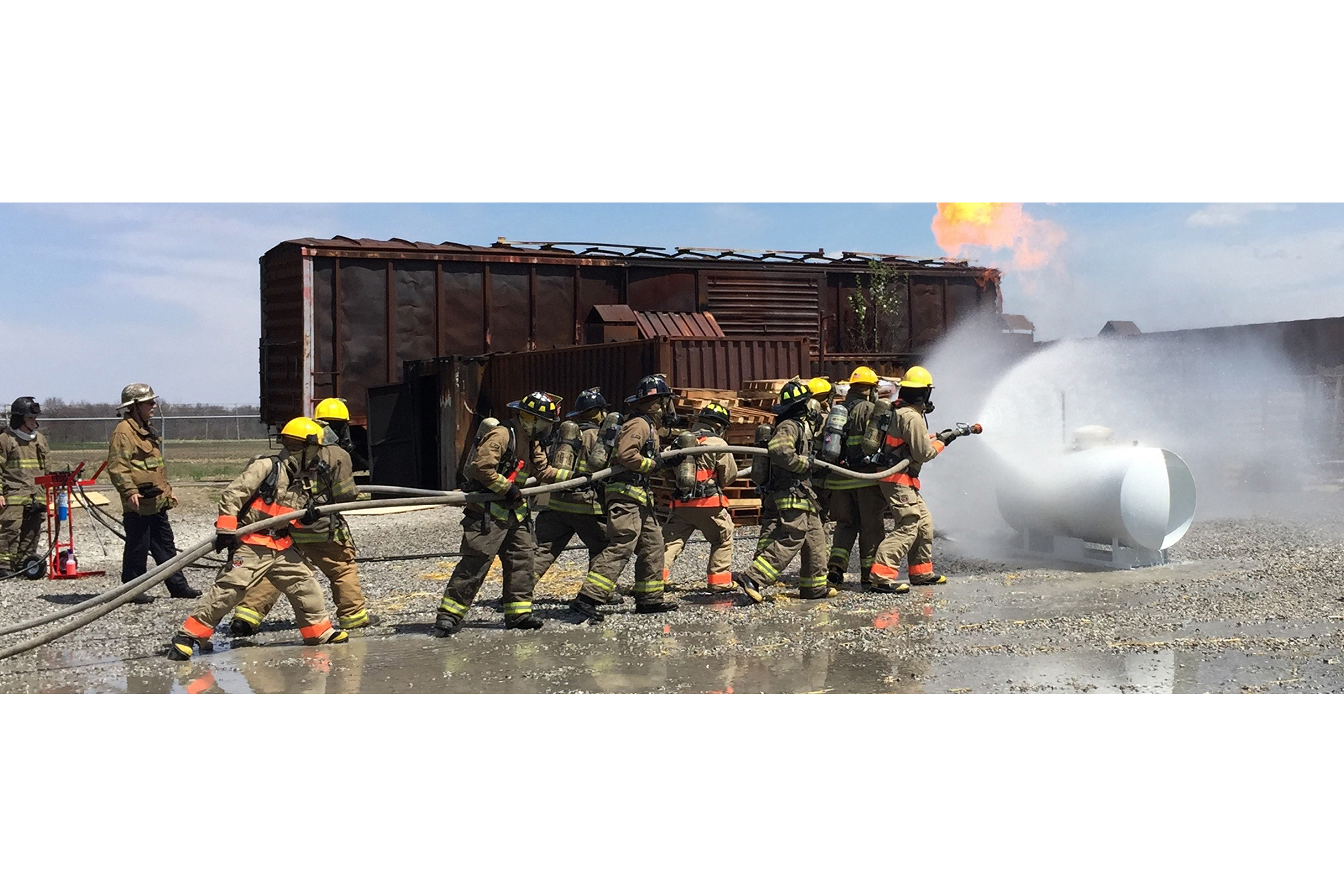 students fire fighters practicing with hose