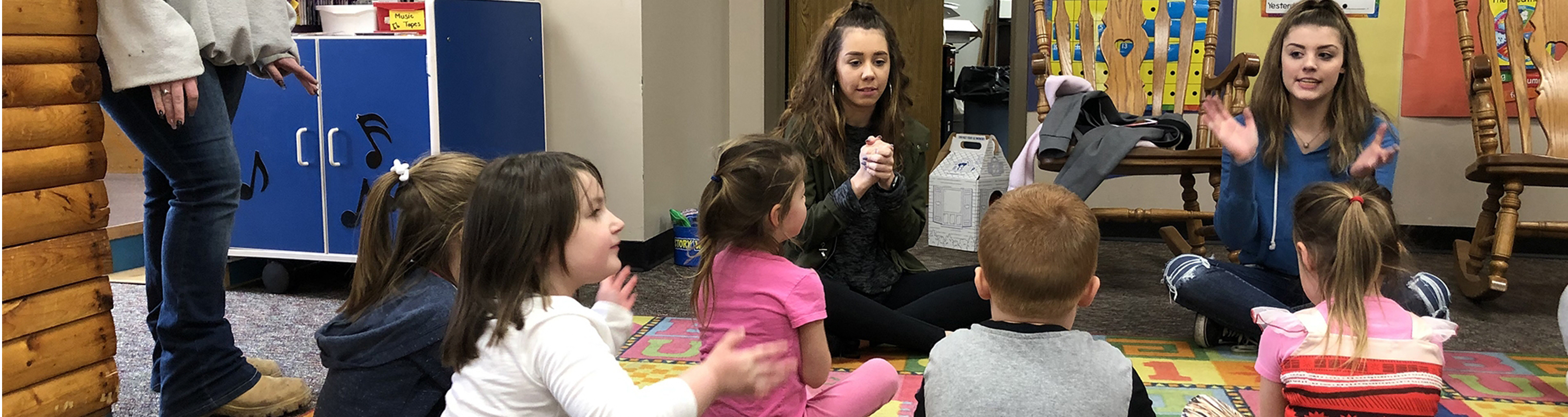 Two teachers sitting on the floor with an early childhood group