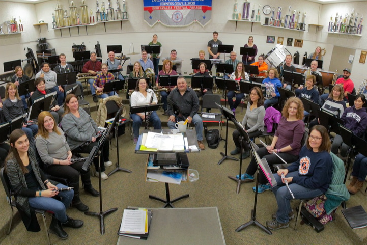 people holding instruments sitting in a band room
