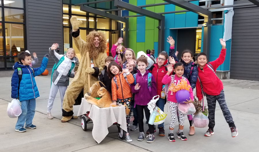students waving in front of school with the principal who is dressed as a lion mascot