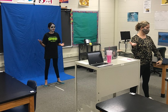 student with face painted standing in front of blue screen with teacher rehearsing for musical