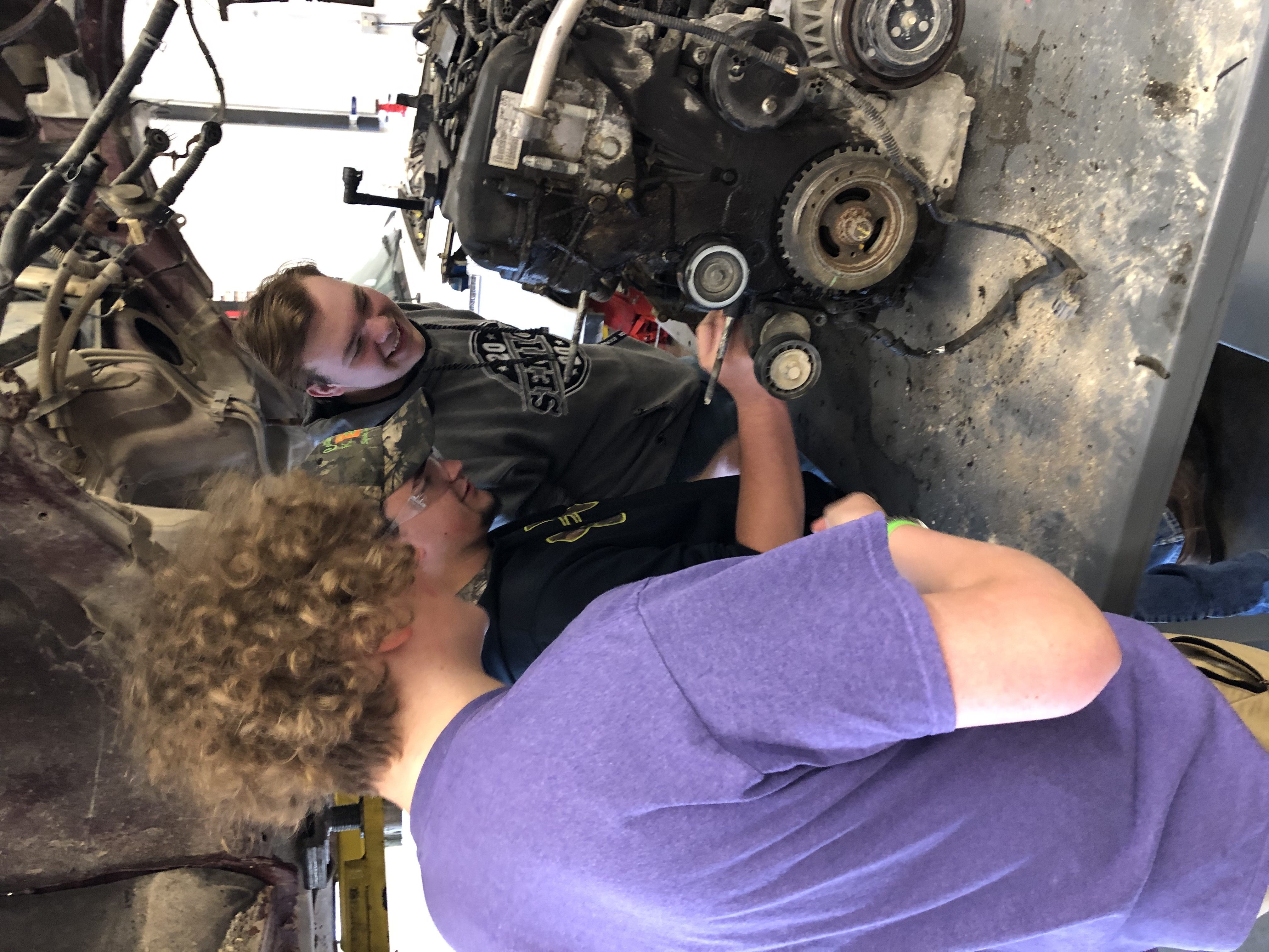 Three students working on an engine