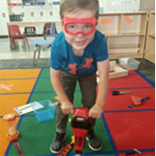 student playing with kid tools