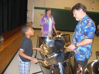 Musician Ted Canning works with a student on playing the steel drums.