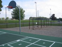 The playground includes an area for basketball, four square, and swings.