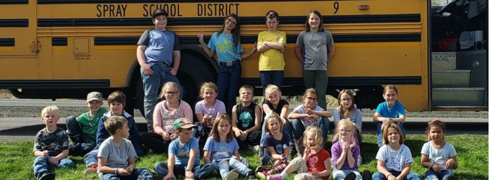 Spray students sitting in front of a school bus