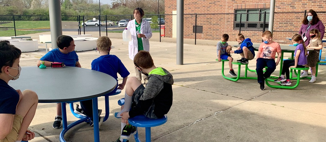Mrs. Ballinger is welcoming Mrs. Colgan's students to The Learning Garden and enlisting their help as she prepares to plant some of the first vegetables and herbs of the season.