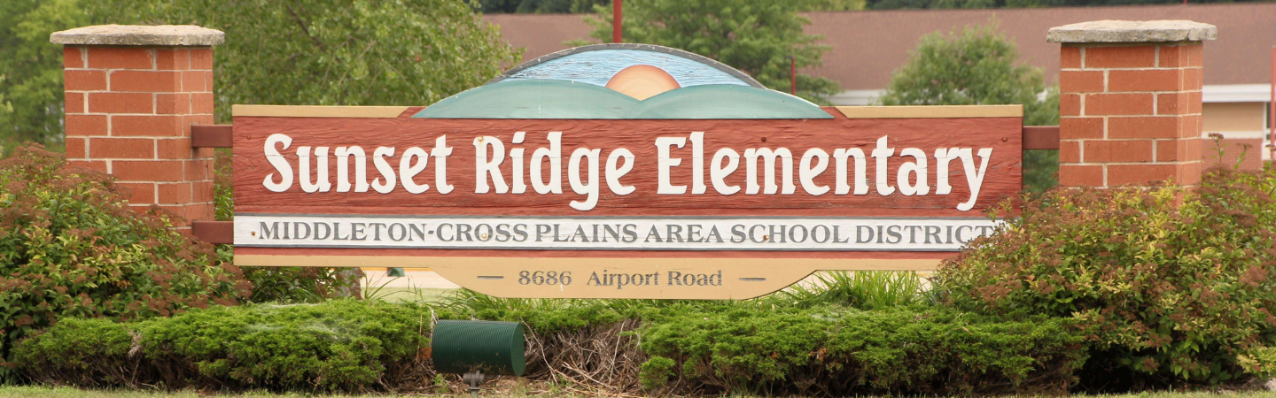 """Picture of the  sign """"Sunset Ridge Elementary"""" school sign. The sign has an image painted on it depicting green hillsides with the sun rising against a blue sky. The school address, 8686 Airport Road is included on the sign."""