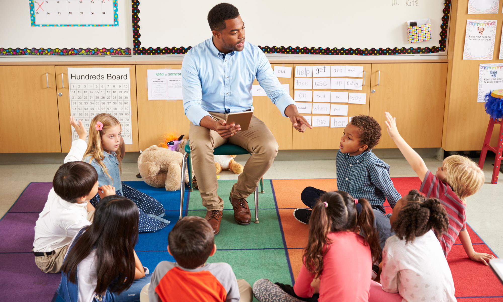 A picture of a male teacher in a elementary classroom