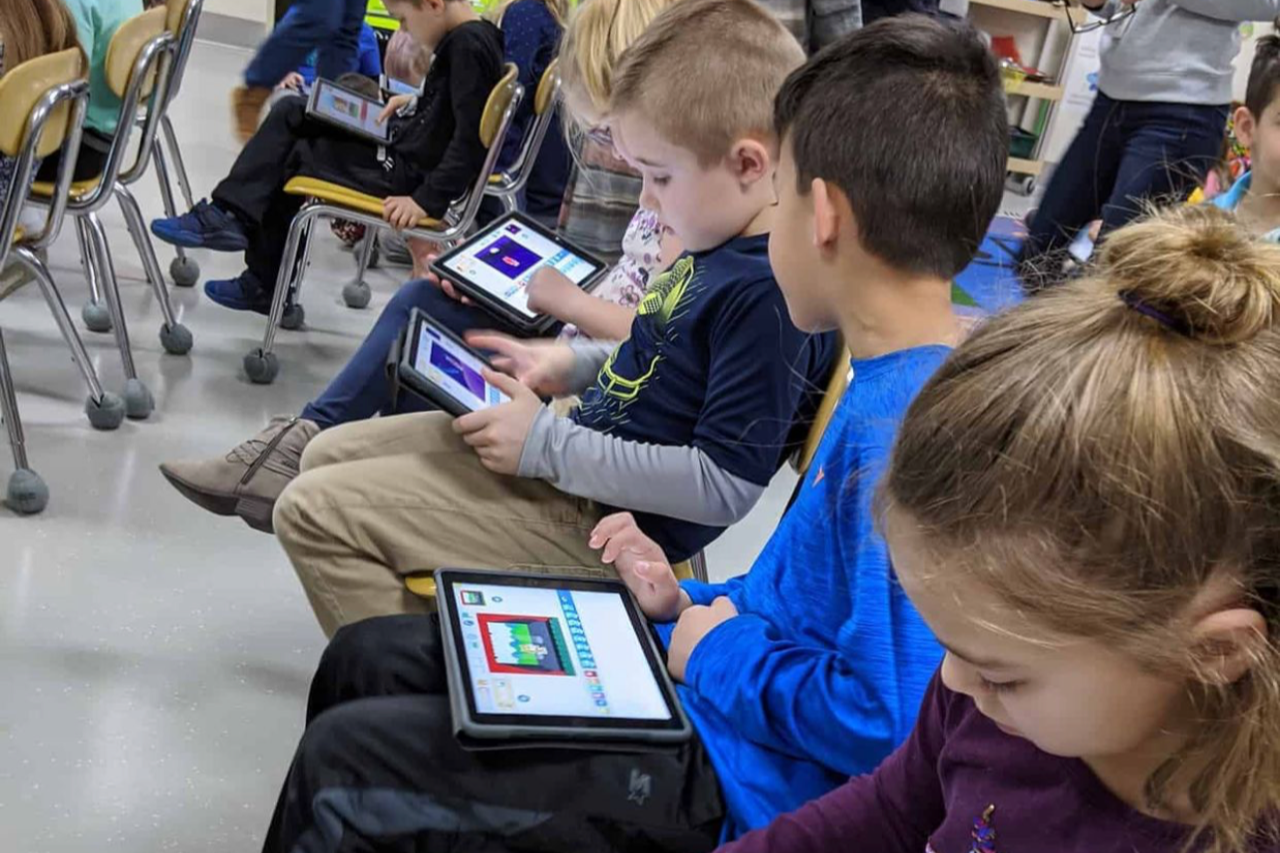 Three Students Using Technology Devices
