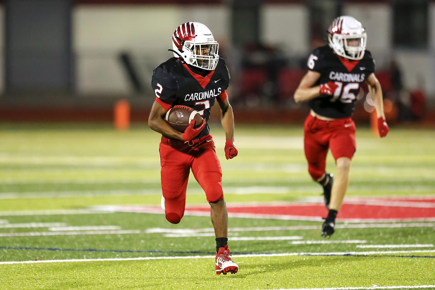 Cardinal football player runs with the ball