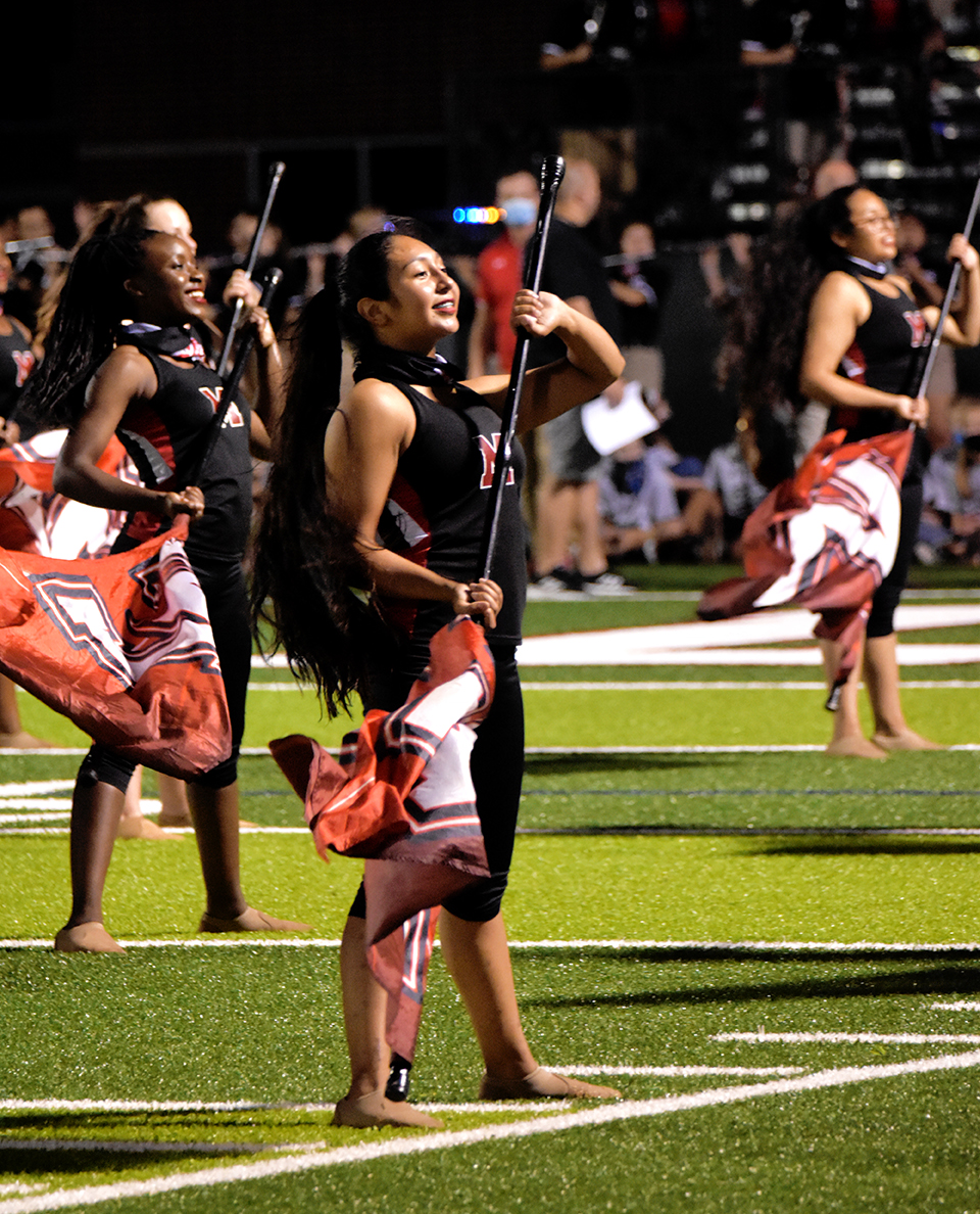 Colorguard student stands with flag during halftime performance