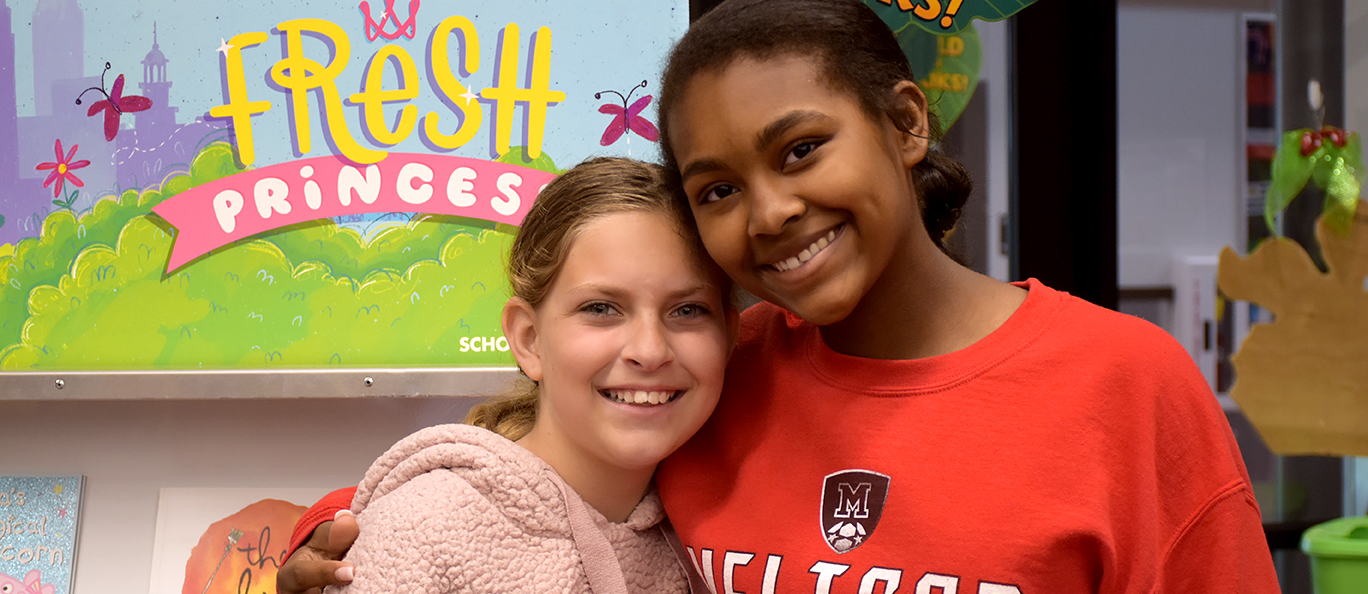 high school student and elementary student pose for a picture at the book fair