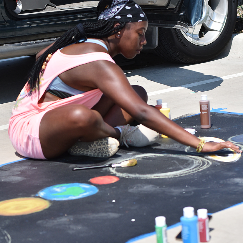Student painting a Senior Reserved parking spot
