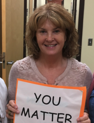 """Ms. Carlson holding a """"you matter"""" sign"""
