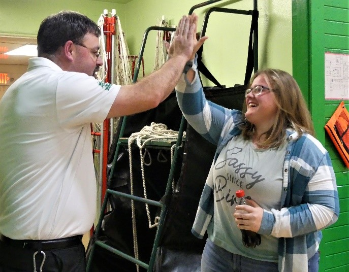 Teacher and student celebrates with a high five.