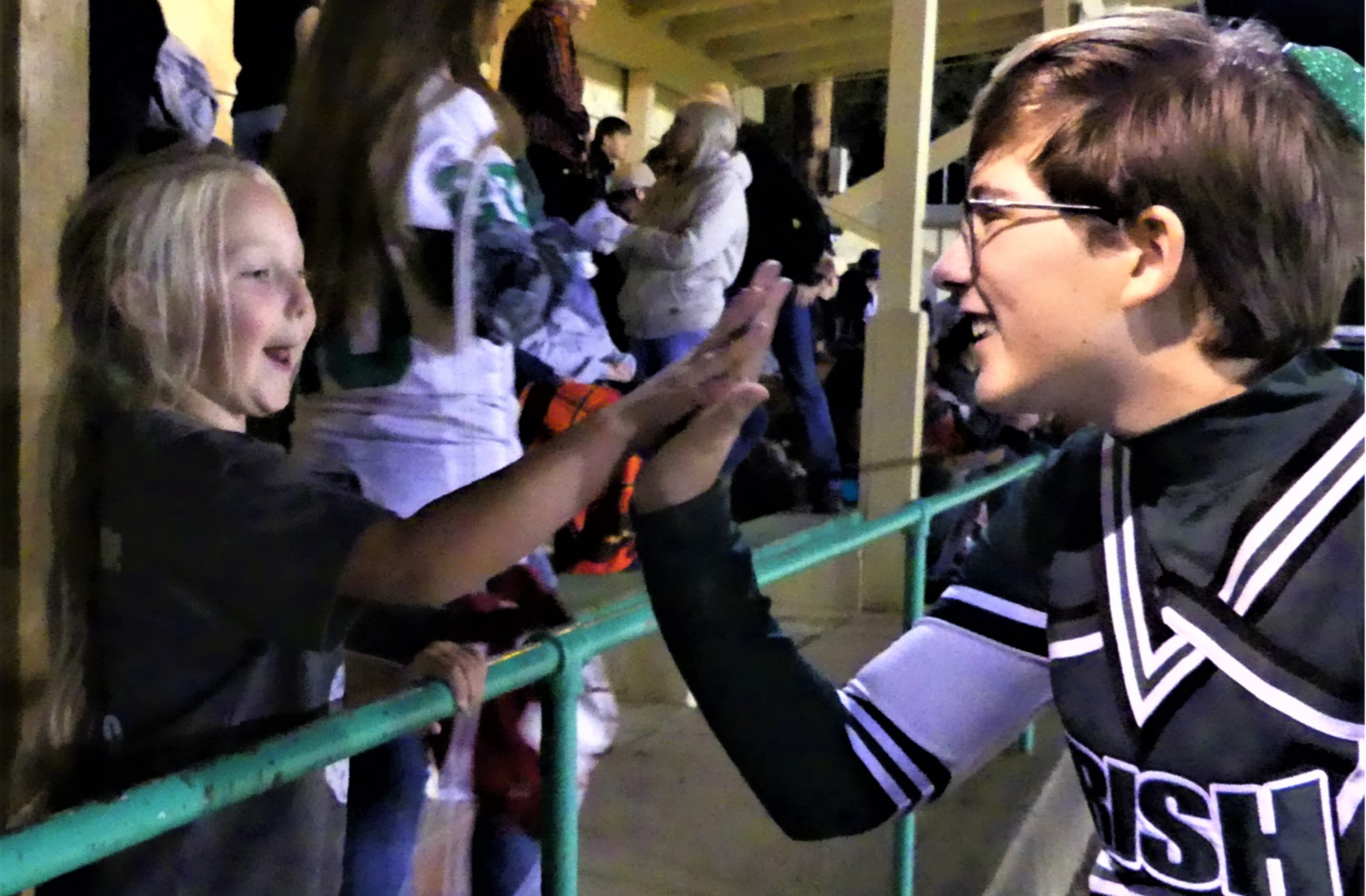 Cheerleader with elementary student at football game.