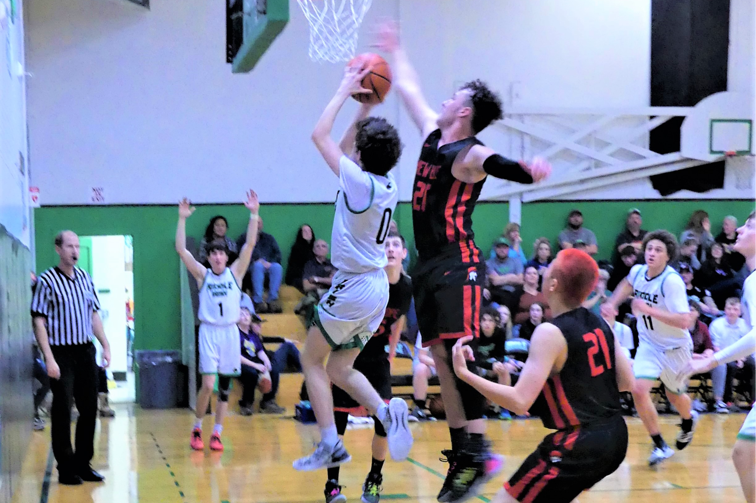 Riddle basketball player going up for a basket.