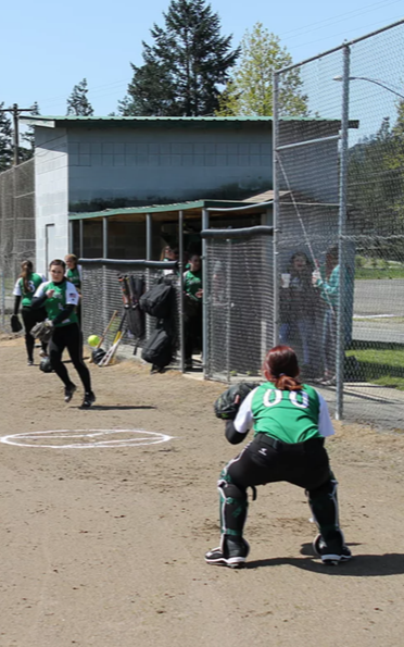 Softball players practice outside dugout