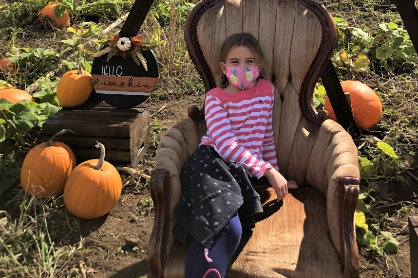 Student sitting at a pumpkin patch