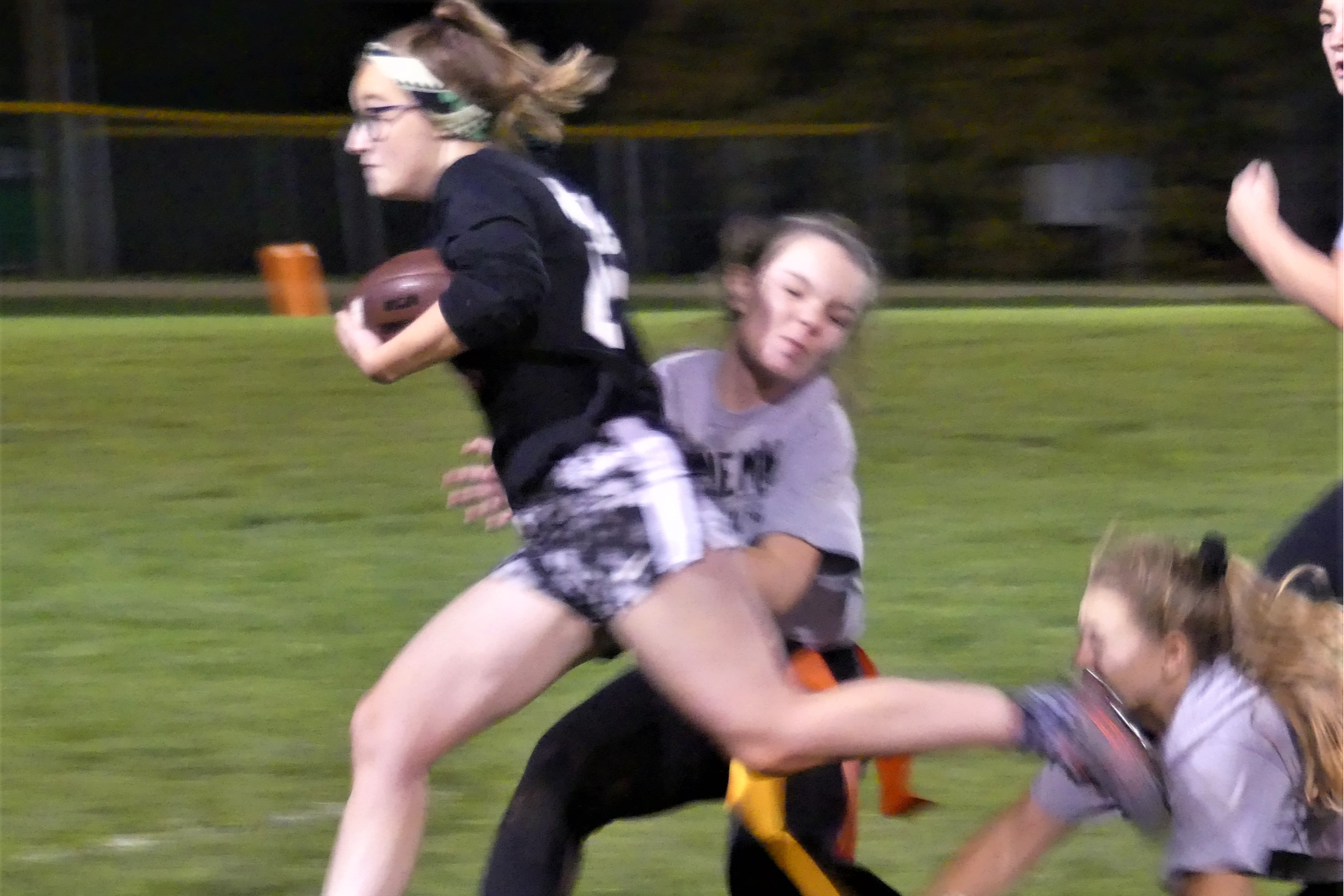Homecoming Powder Puff Game. Team grabs for the flags of the running back. The running back's left foot makes contact with a player on the opposing team.