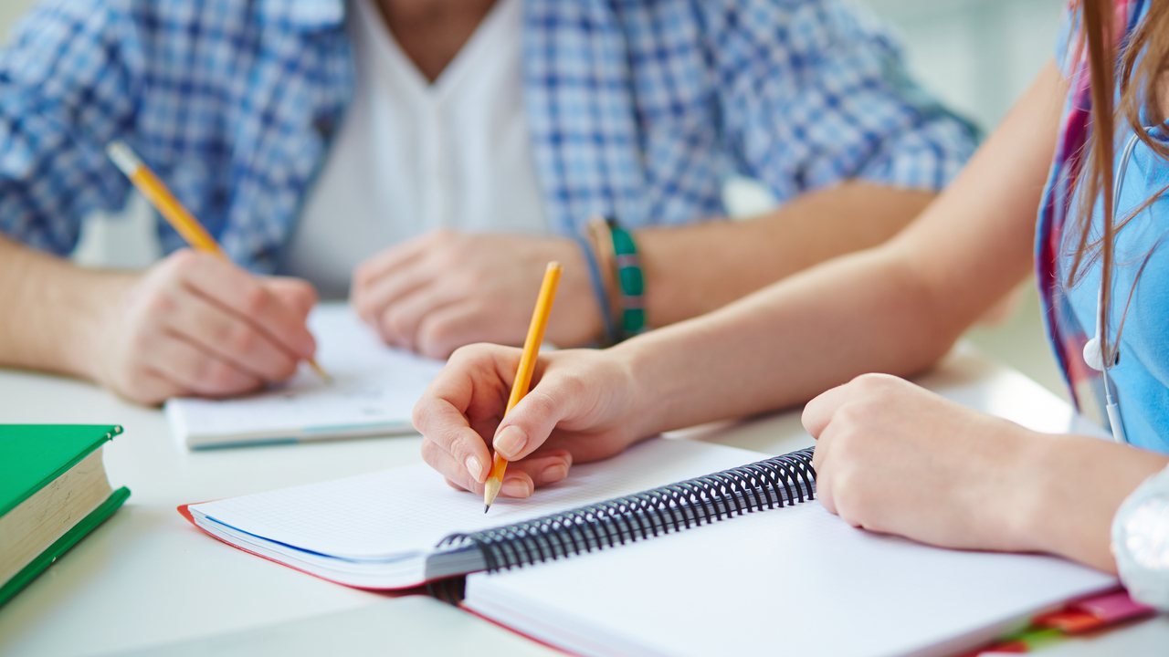 Students write on notebooks.