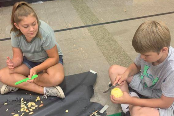Campers making Apple Head Dolls.