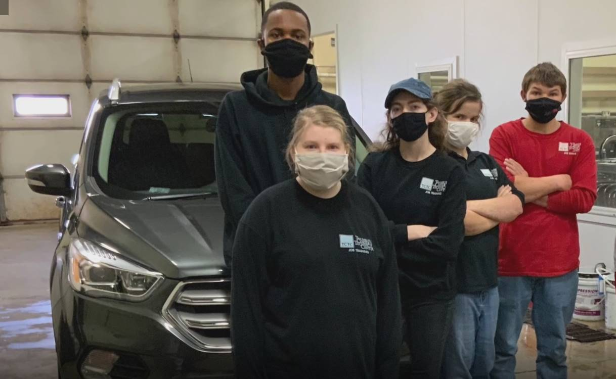 Students with masks standing in front of a car