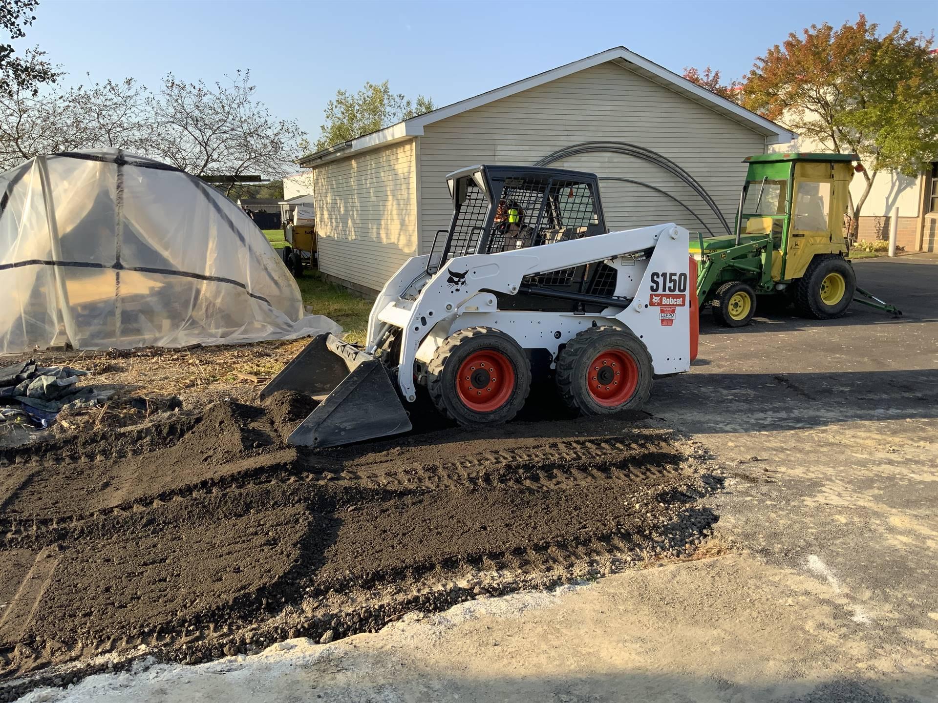 Heavy machinery scooper moving dirt