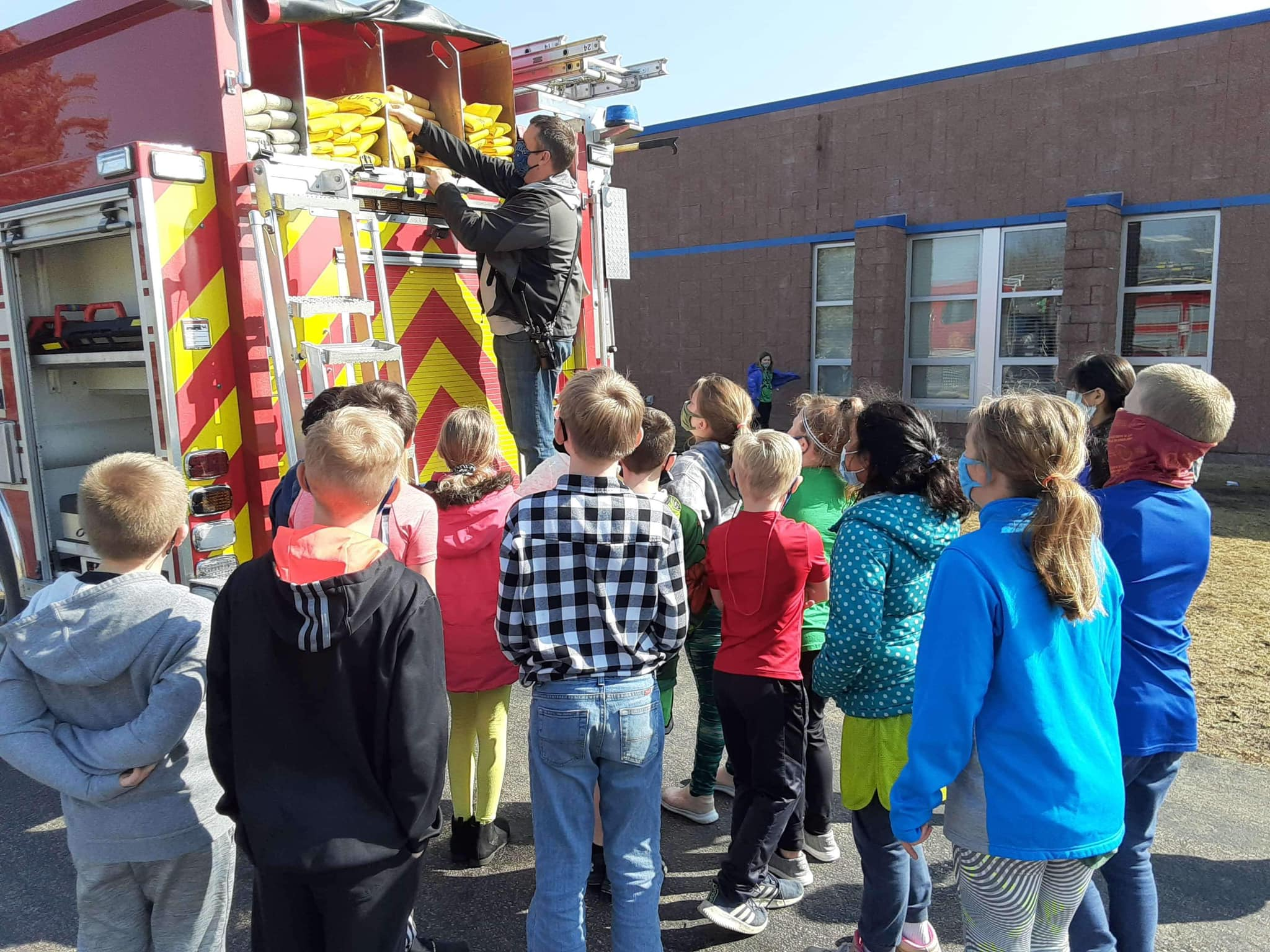 Students looking at someone on a firetruck