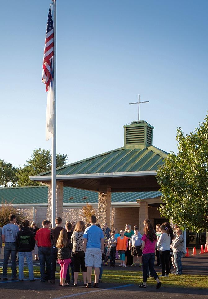 Students praying around a flag pole