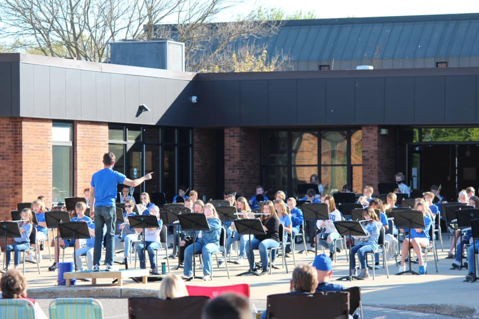 Picture of Plainwell Middle School band concert outside in front of Plainwell Middle School.  Students are wearing blue shirts.