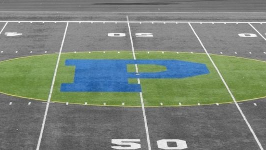 """Black and white picture of football field with Plainwell """"P"""" highlighted in green and blue."""