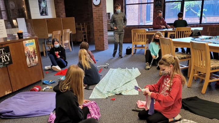 Students in library making fleece blankets for the community.