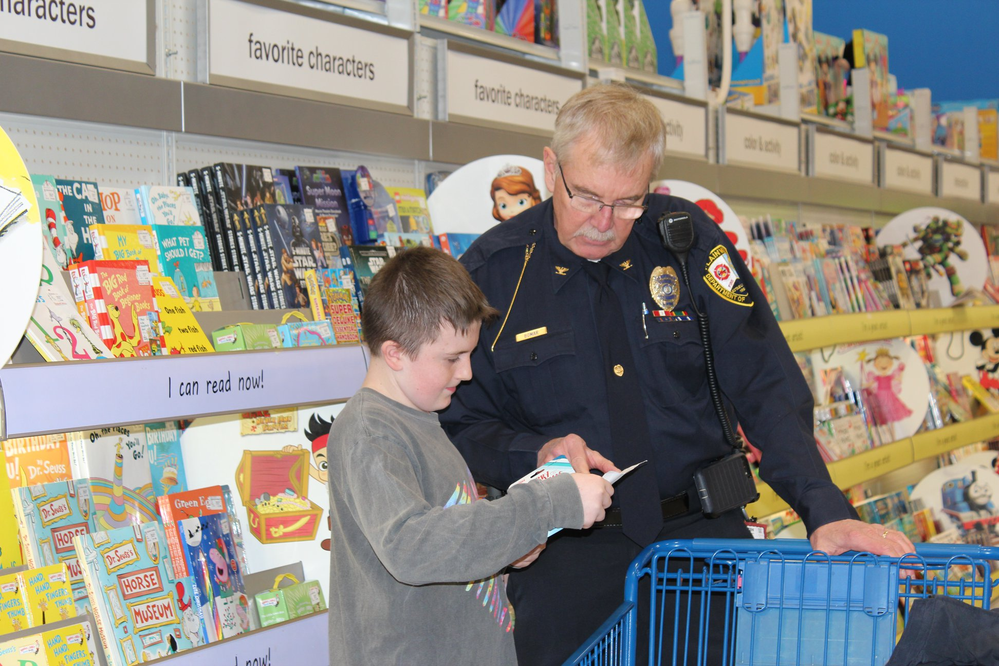 Picture of a police officer helping a student shopping at Meijer for the annual Shop with a Hero event.