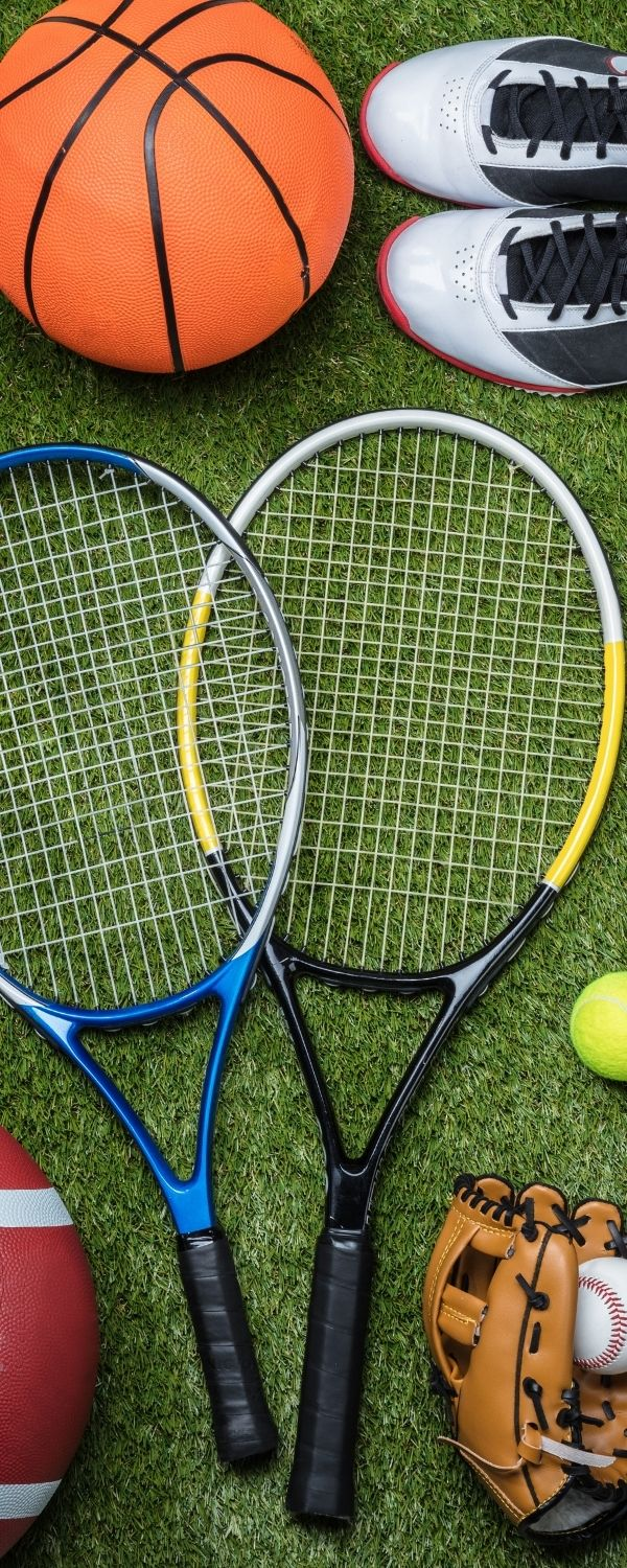 Grass background with sports equipment (tennis racket, shoes, football, baseball and glove