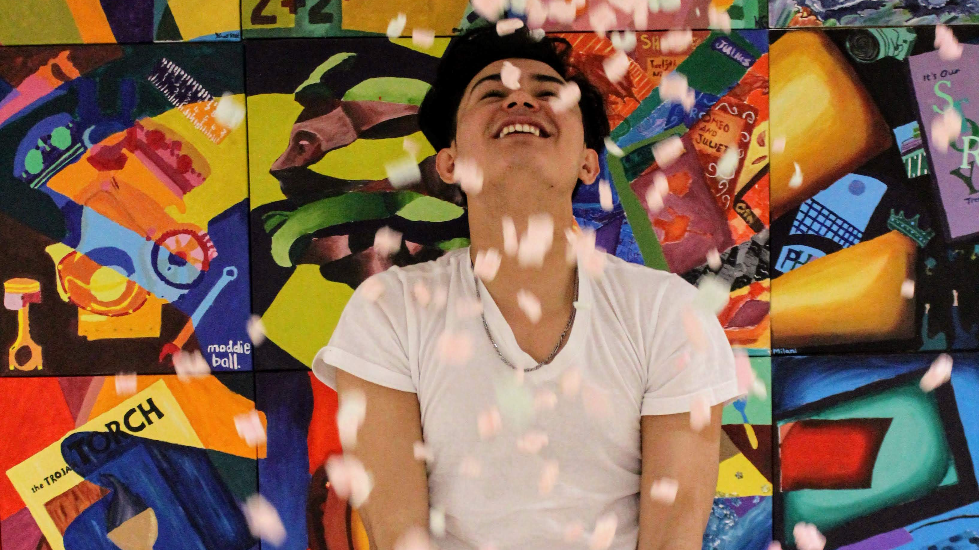 Picture of student throwing confetti in front of a color backdrop