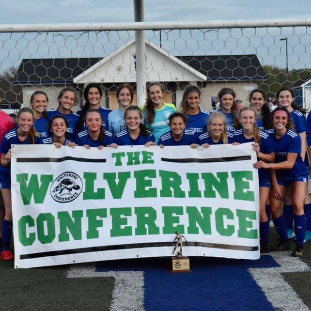 Picture of women's soccer team holding a Wolverine Conference banner