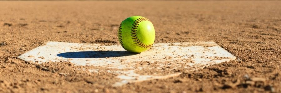Picture of a softball field with a base and yellow softball
