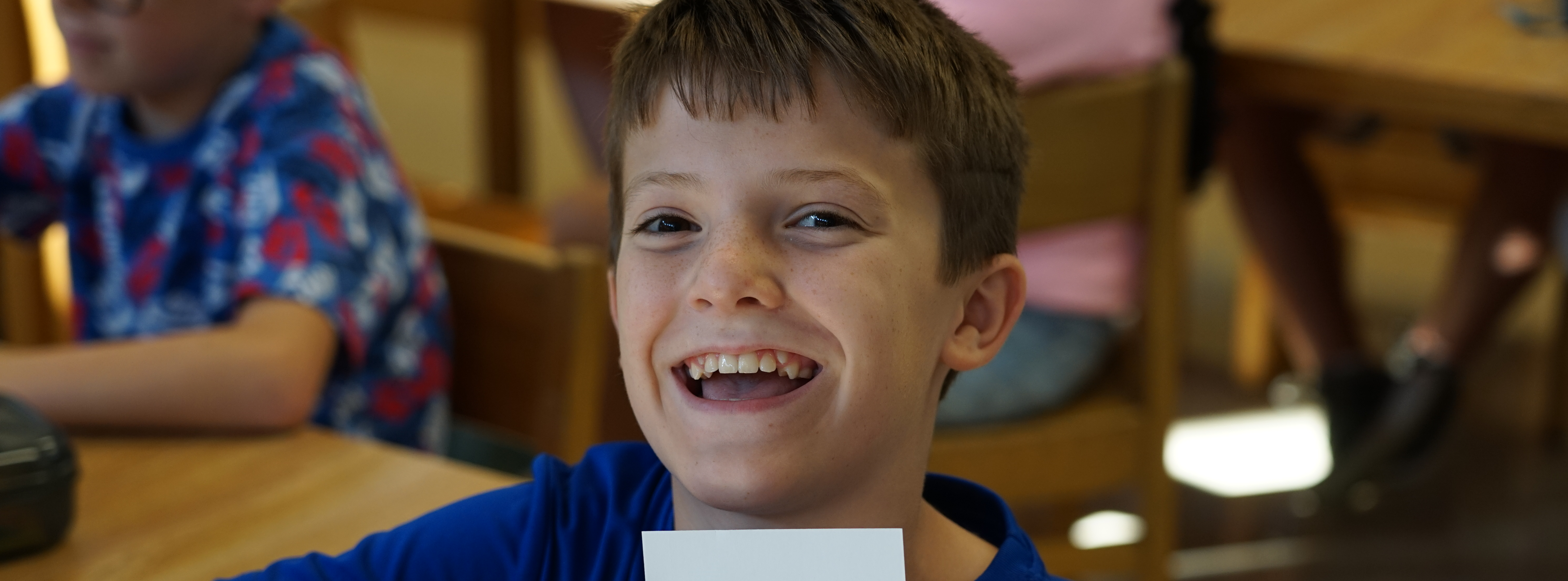 Boy in library posing and smiling at camera