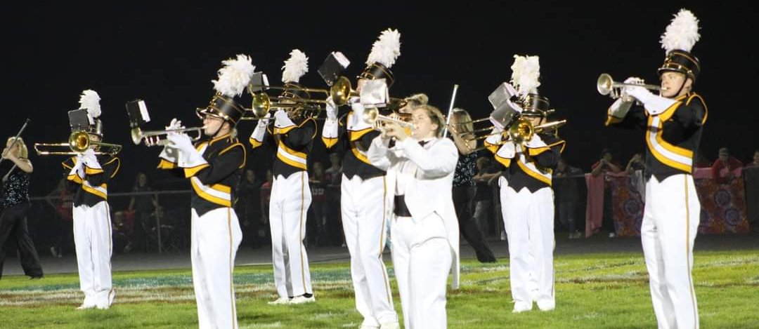 Marching band in their uniforms playing on the football field