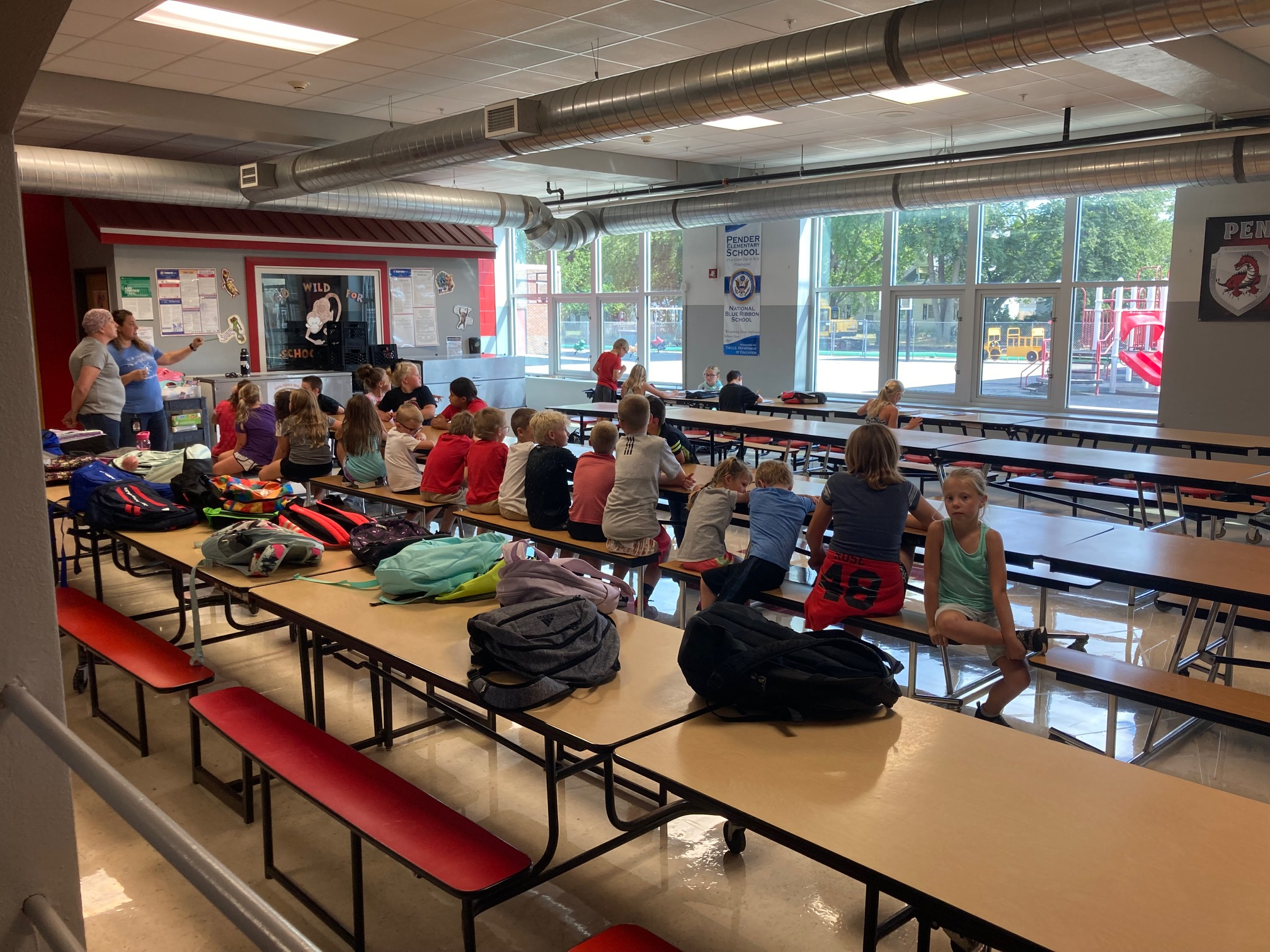 more kids sitting at lunch tables while being supervised by adults nearby
